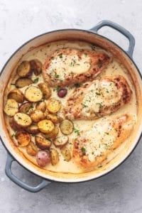 chicken and potatoes with creamy sauce and fresh herbs in a skillet