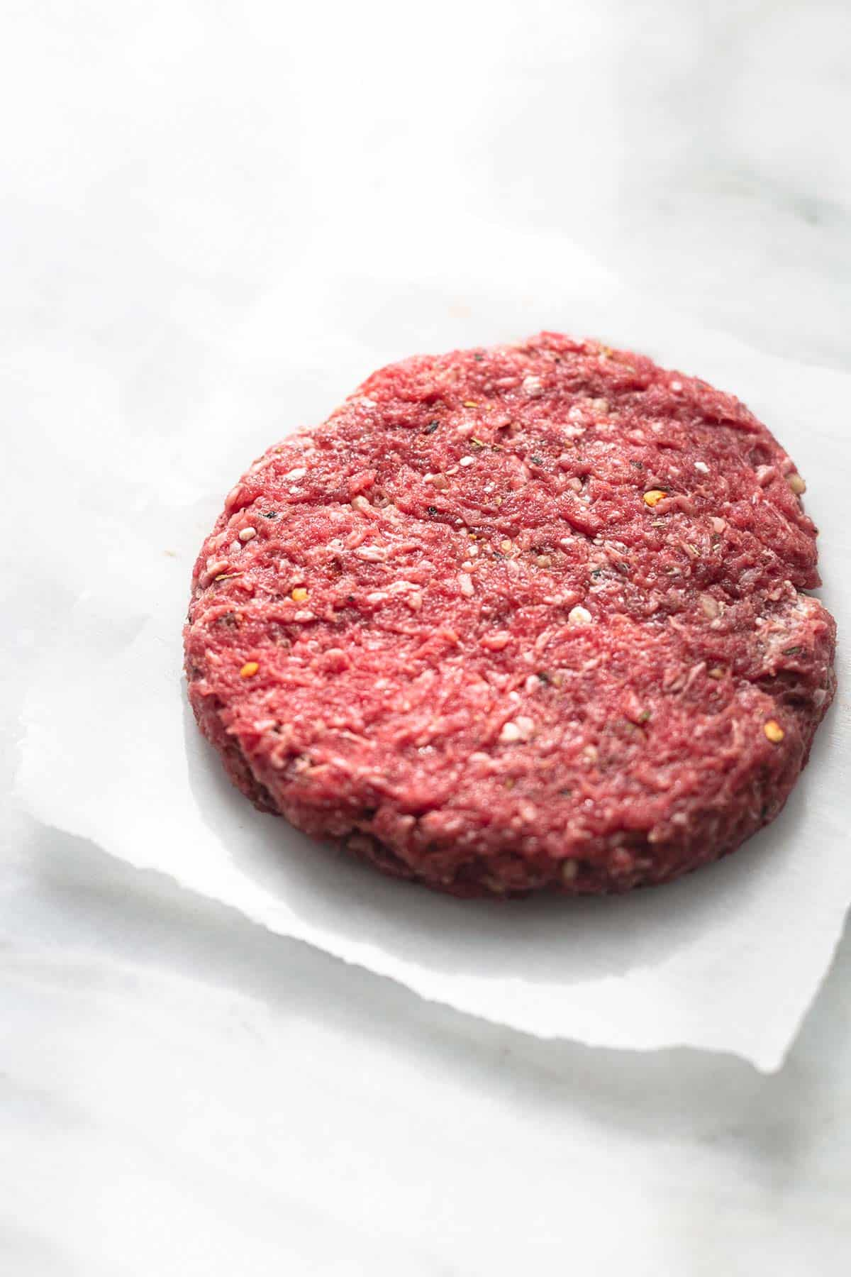 single ground beef patty on parchment paper