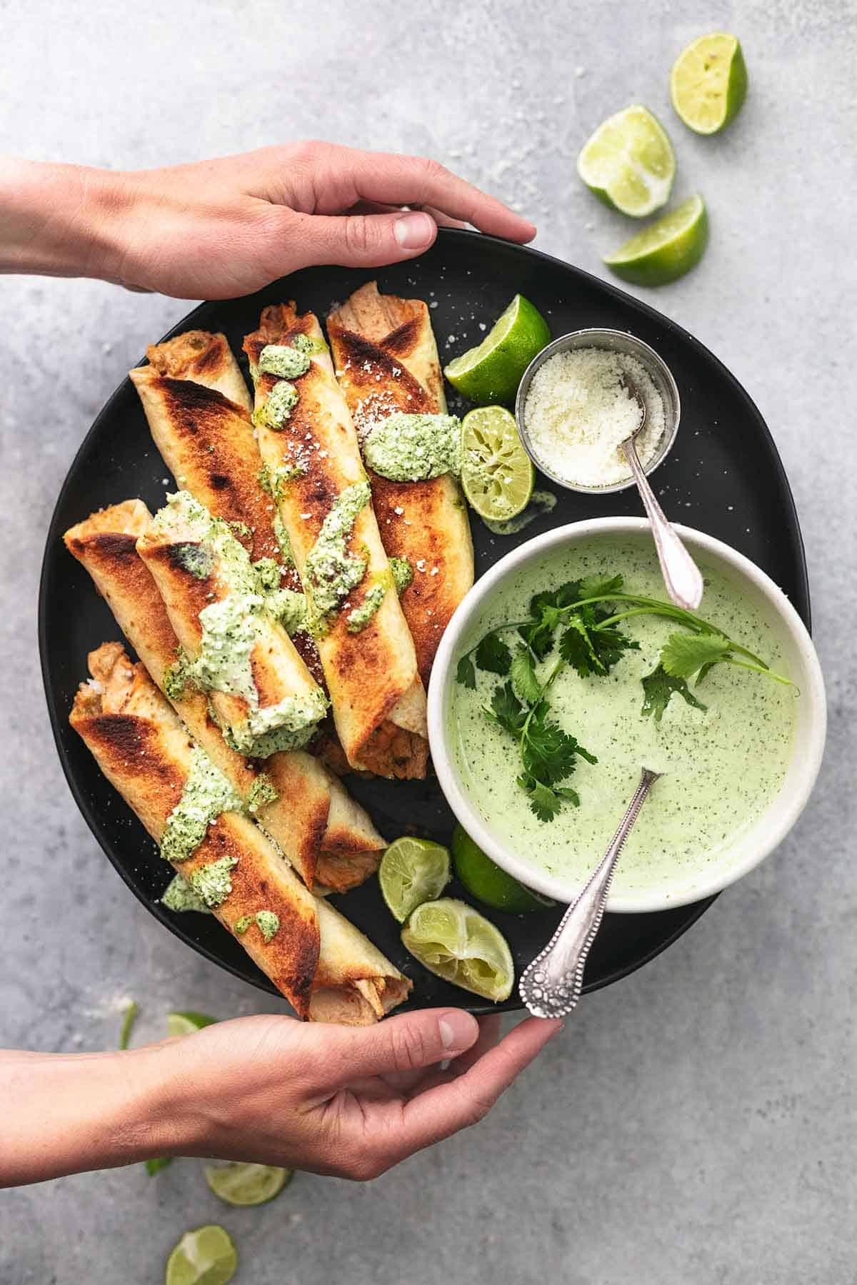 hands holding plate of taquitos