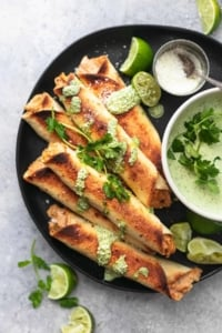 overhead taquitos on black plate with limes and green sauce