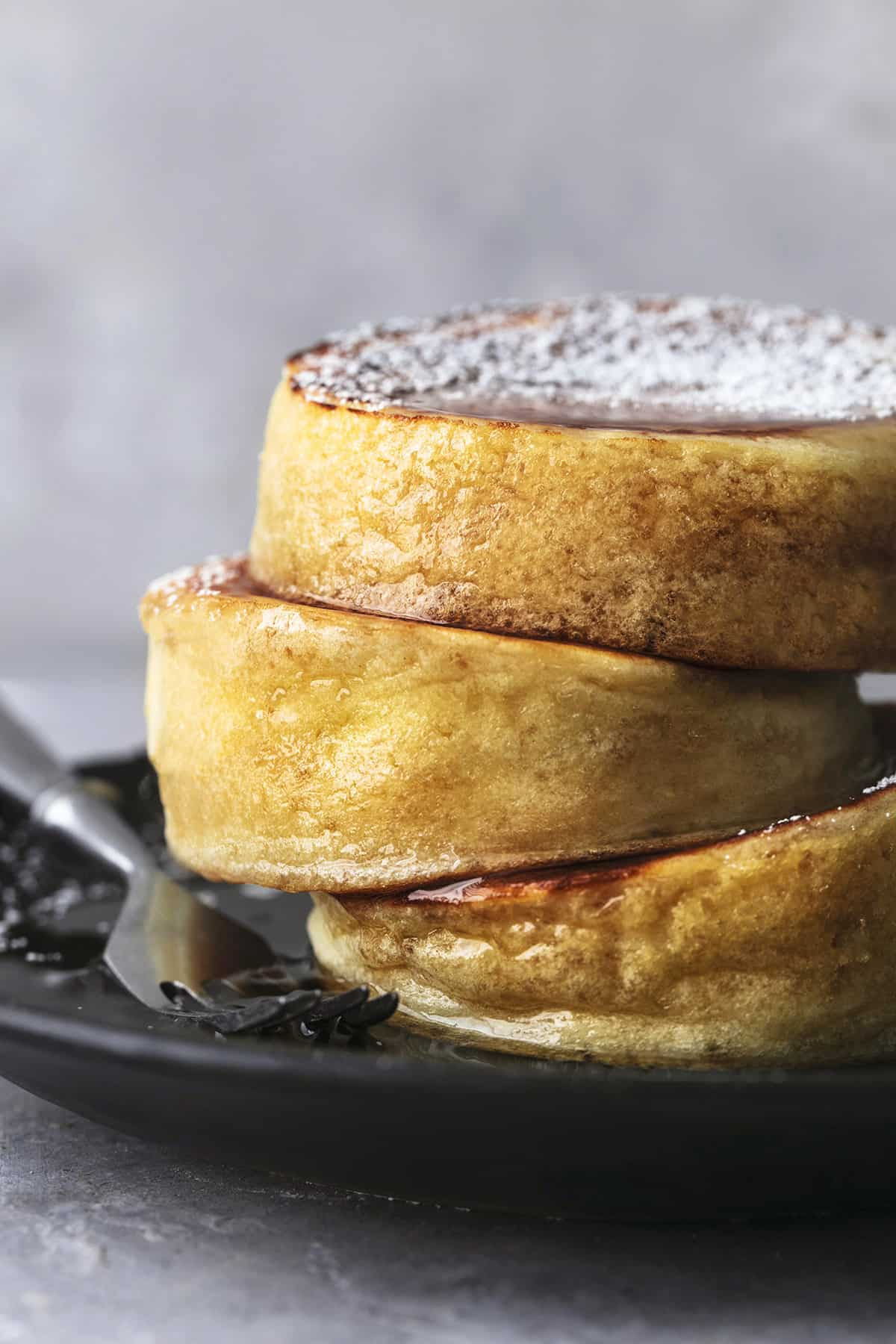 up close stacked japanese souffle pancakes on plate with fork