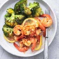 overhead shrimp and broccoli with lemon slices on white plate with fork