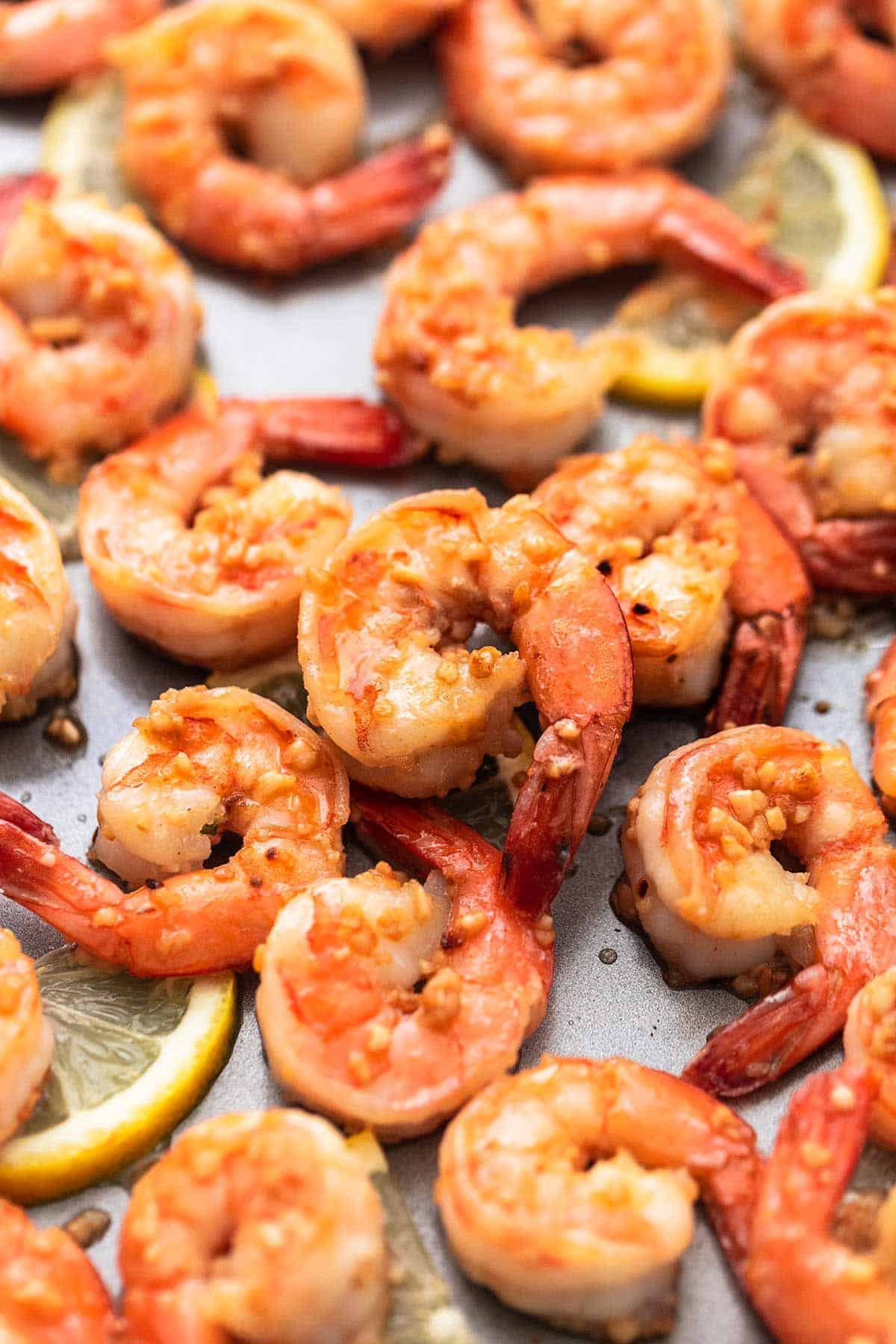 close up of cooked shrimp with lemon and garlic on a sheet pan.