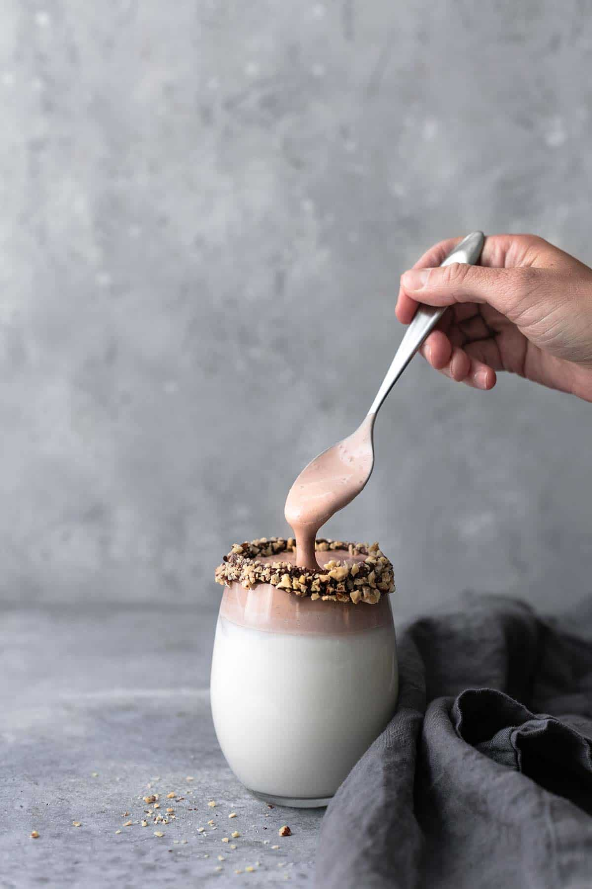 a hand picking up a spoon from a glass of whipped milk: three ways.