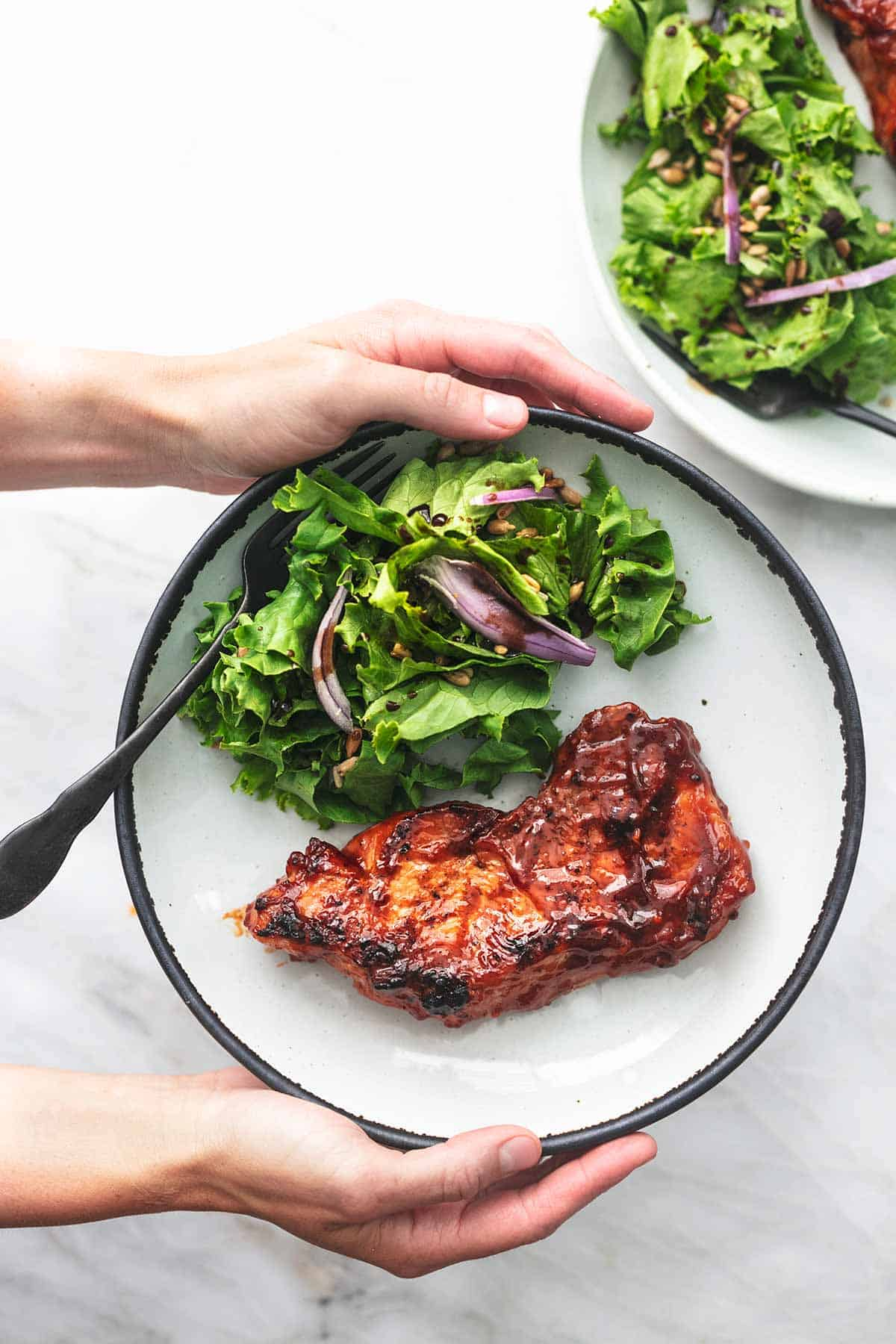 overhead view of hands holding plate with grilled bbq pork chop and lettuce