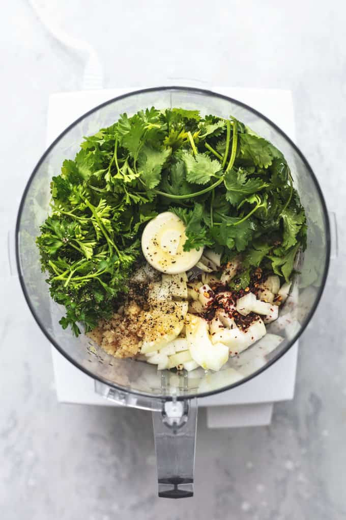 overhead view of ingredients for chimichurri sauce inside of food processor