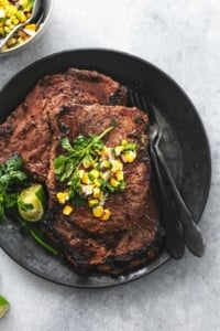 overhead view of cooked steak on plate topped with corn salsa