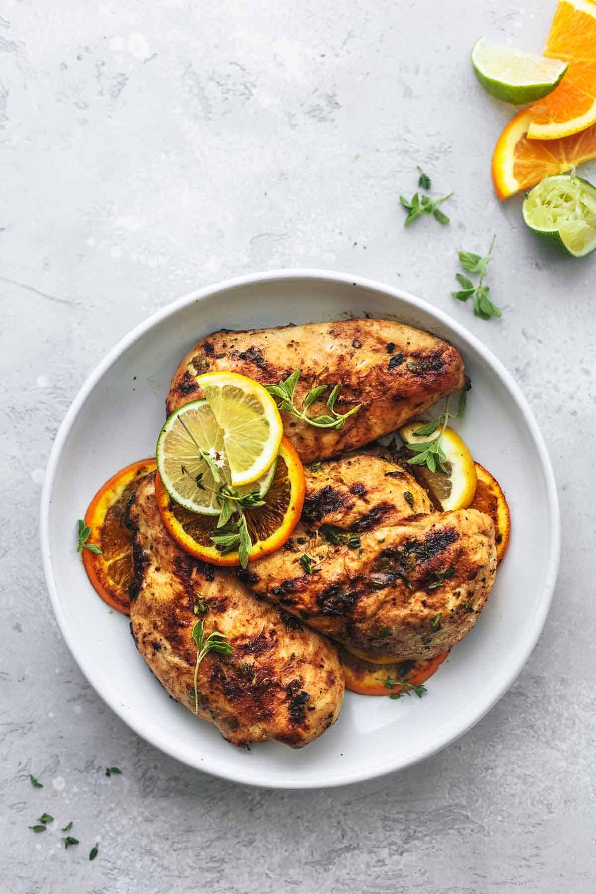 overhead view of grilled chicken on a white plate with lemon, lime, and orange slices