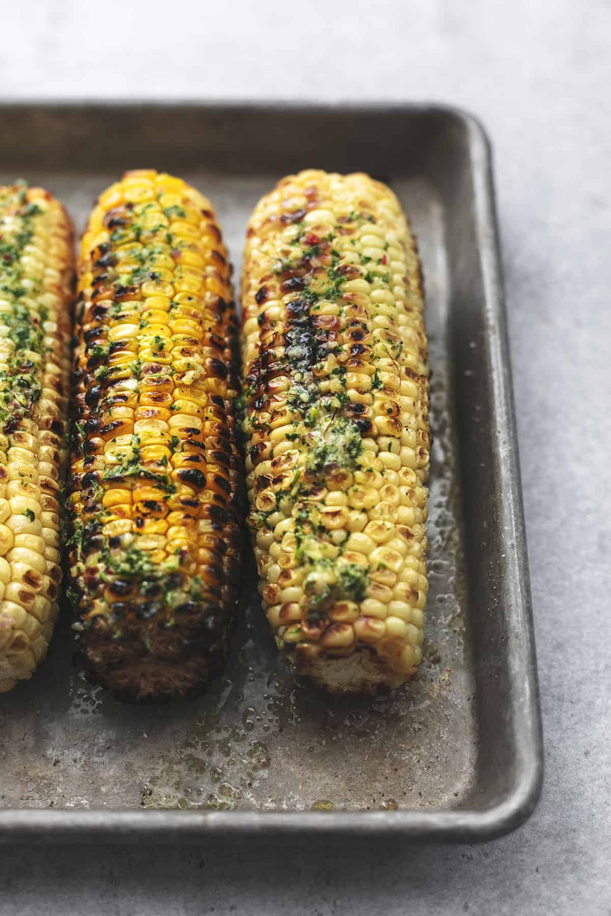 45 degree angle of grilled corn on cob with butter and herbs
