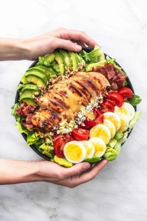 hands holding bowl of salad with avocado, bacon, chicken, tomatoes, cheese, hard boiled eggs