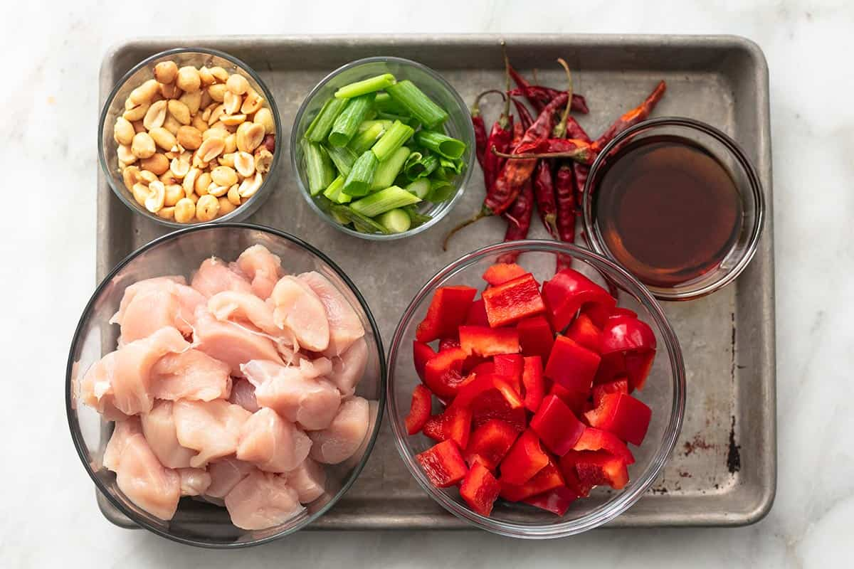 top view of a baking sheet with ingredients for kung pao chicken on it.