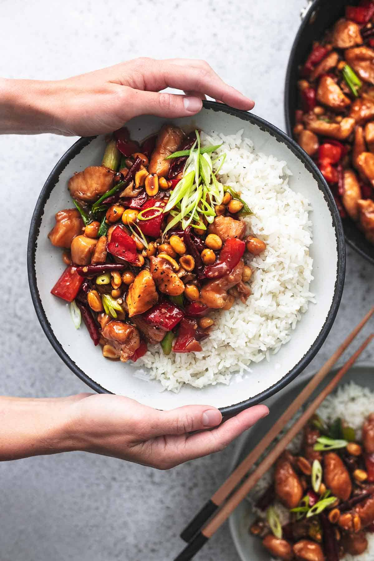 top view of hands holding a plate of kung pao chicken with rice.