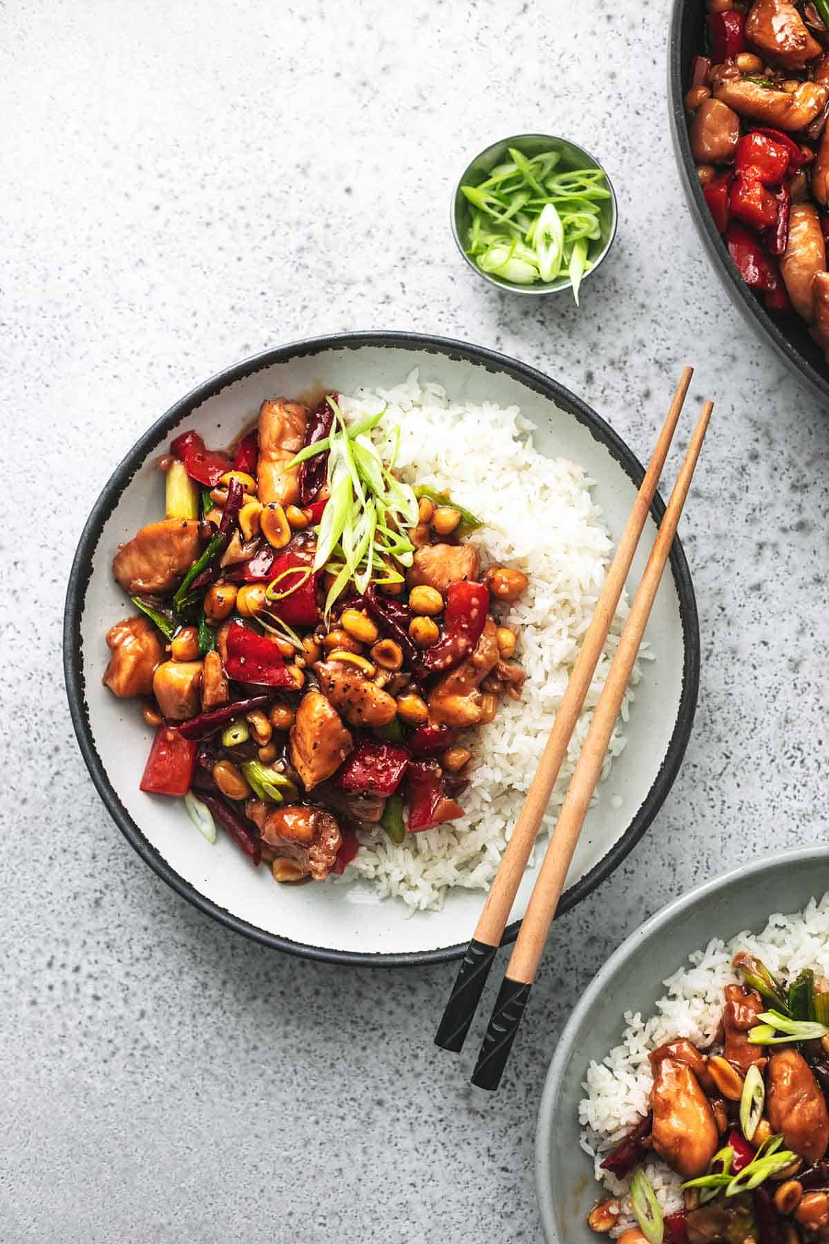 top view of kung pao chicken with white rice in a bowl with chopsticks.