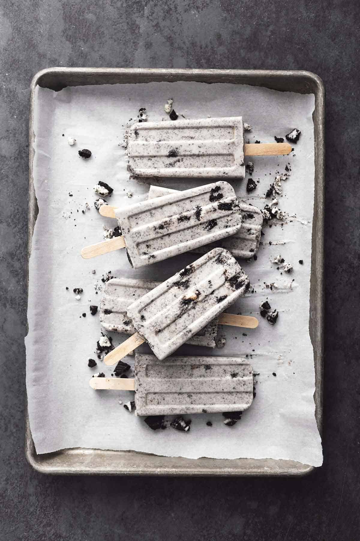 pile of oreo popsicles on a parchment lined baking sheet