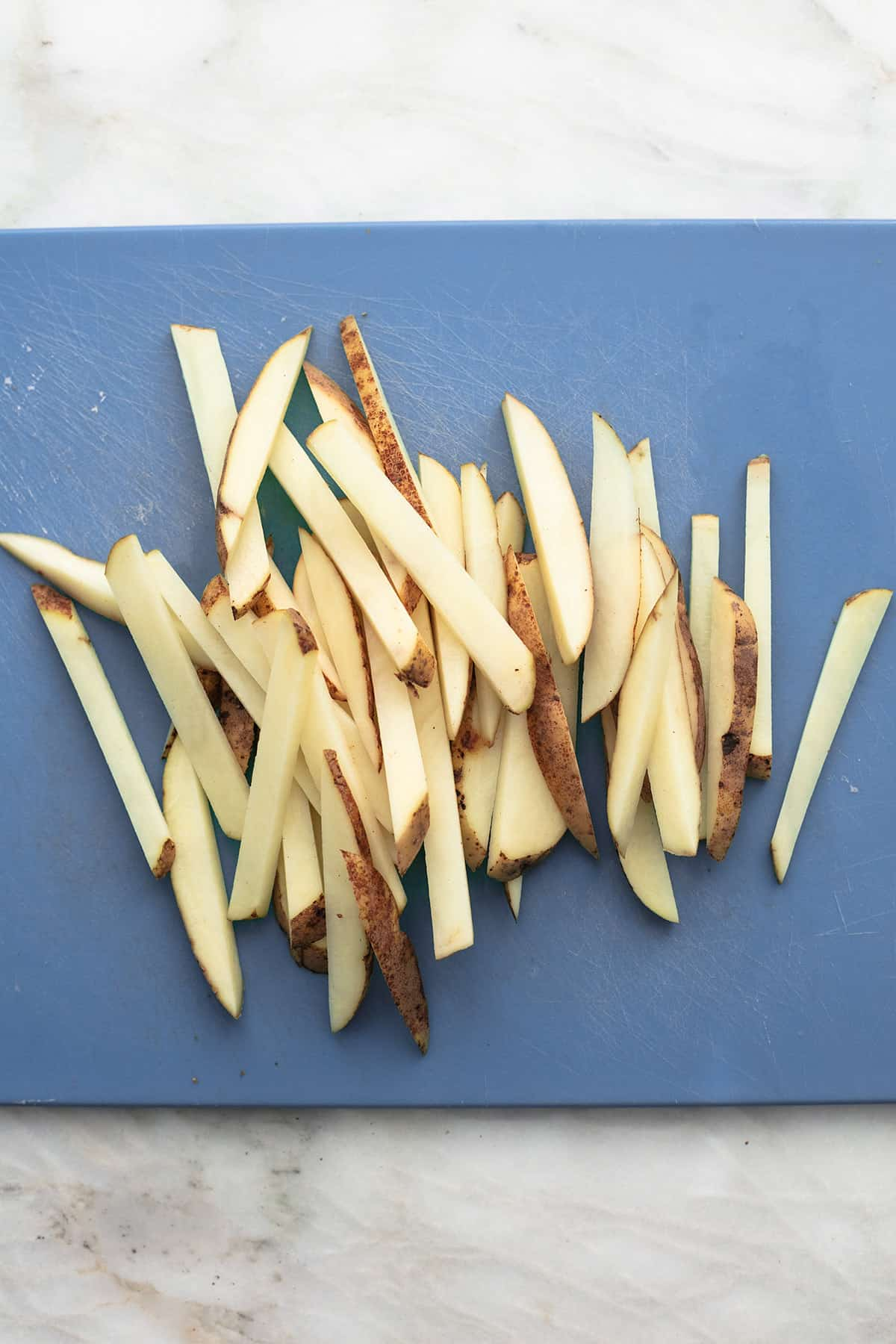 sliced potatoes on blue cutting board