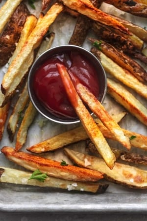 up close overhead french fries on sheet pan with ketchup in cup