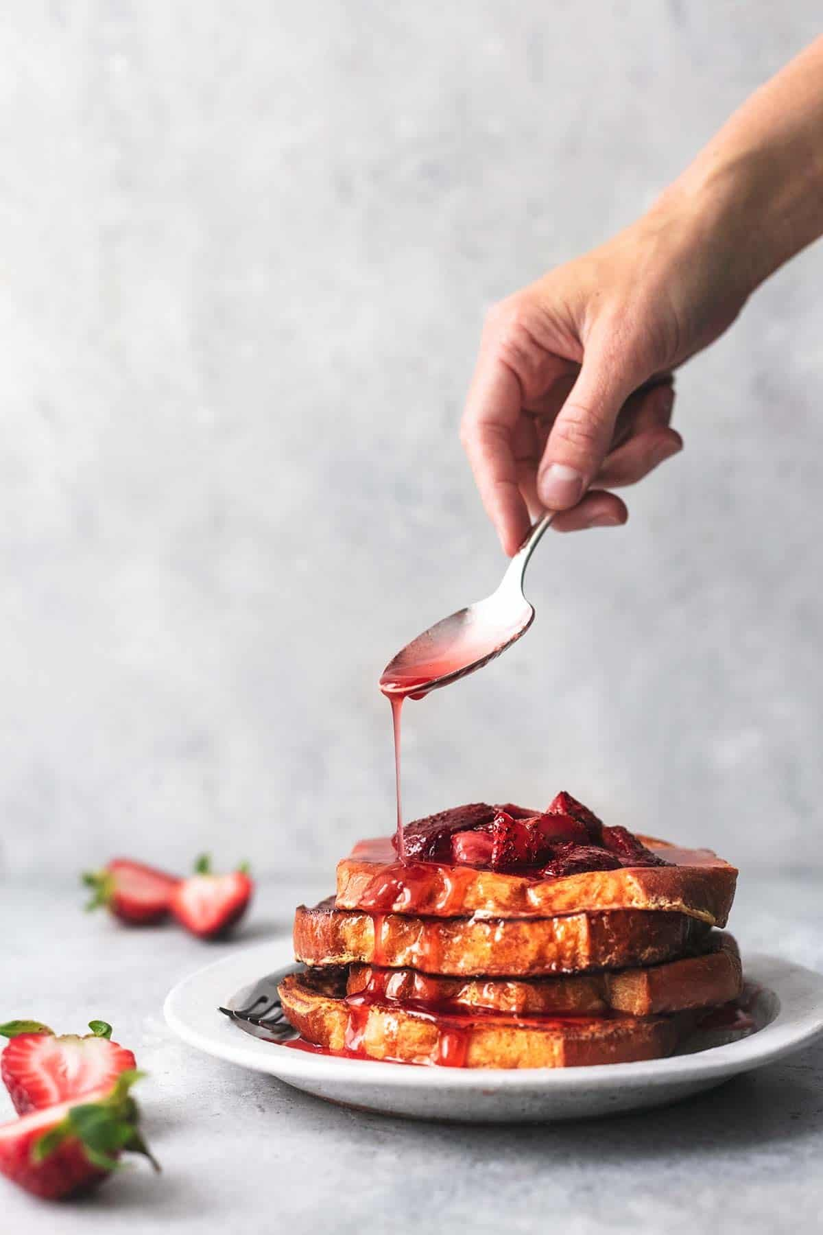 hand holding spoon and drizzling strawberry sauce onto stack of french toast