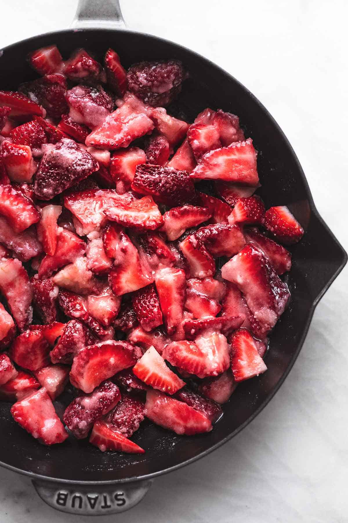 overhead view of sugared sliced strawberries in cast iron skillet