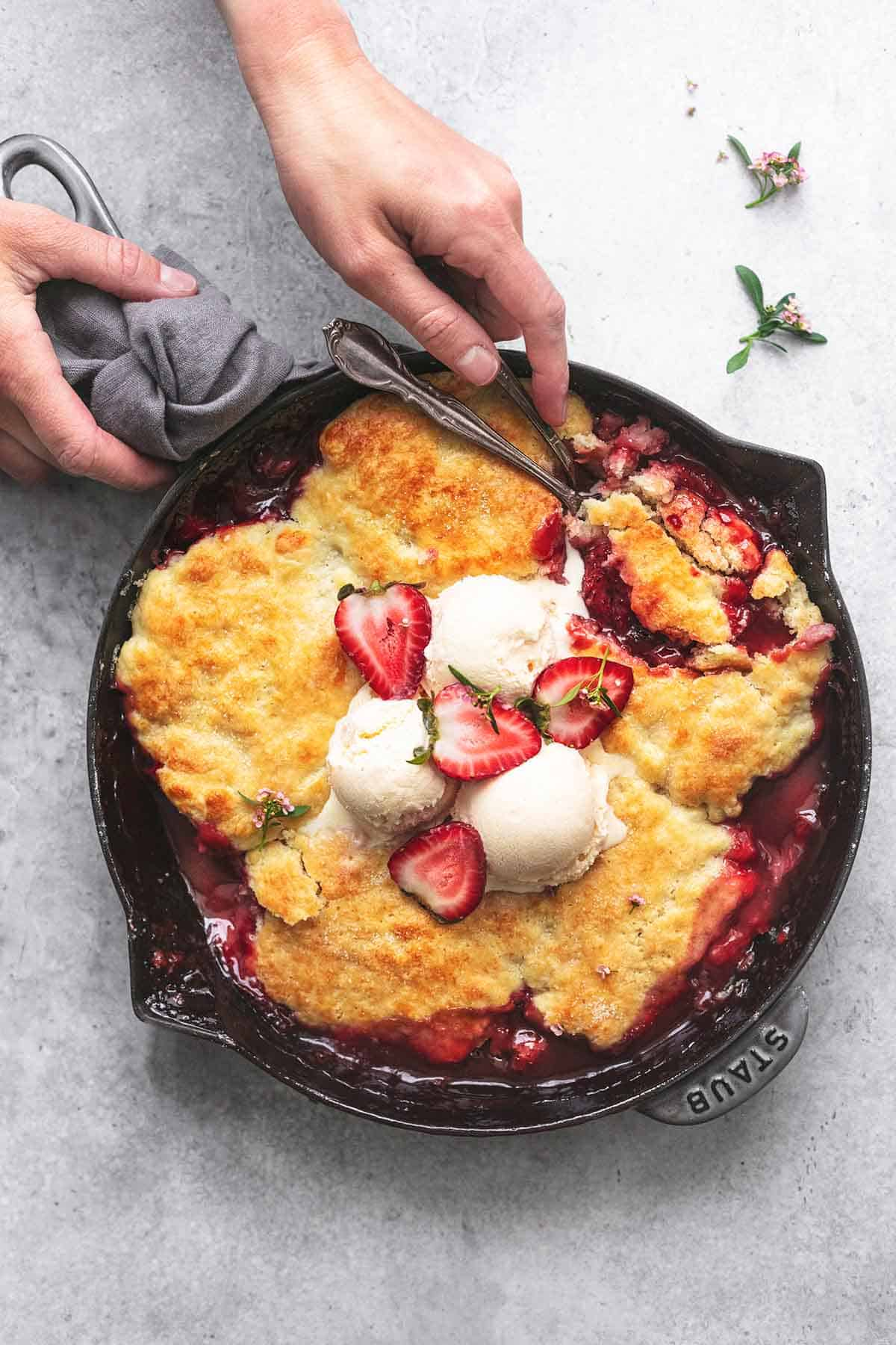 overhead view of hands serving skillet full of baked strawberry cobbler