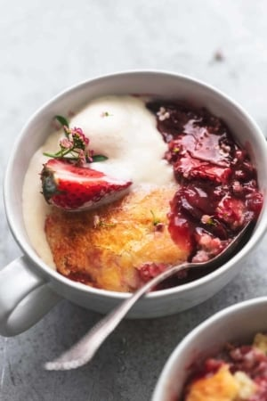 up close view of strawberry cobbler with ice cream in a bowl with a spoon