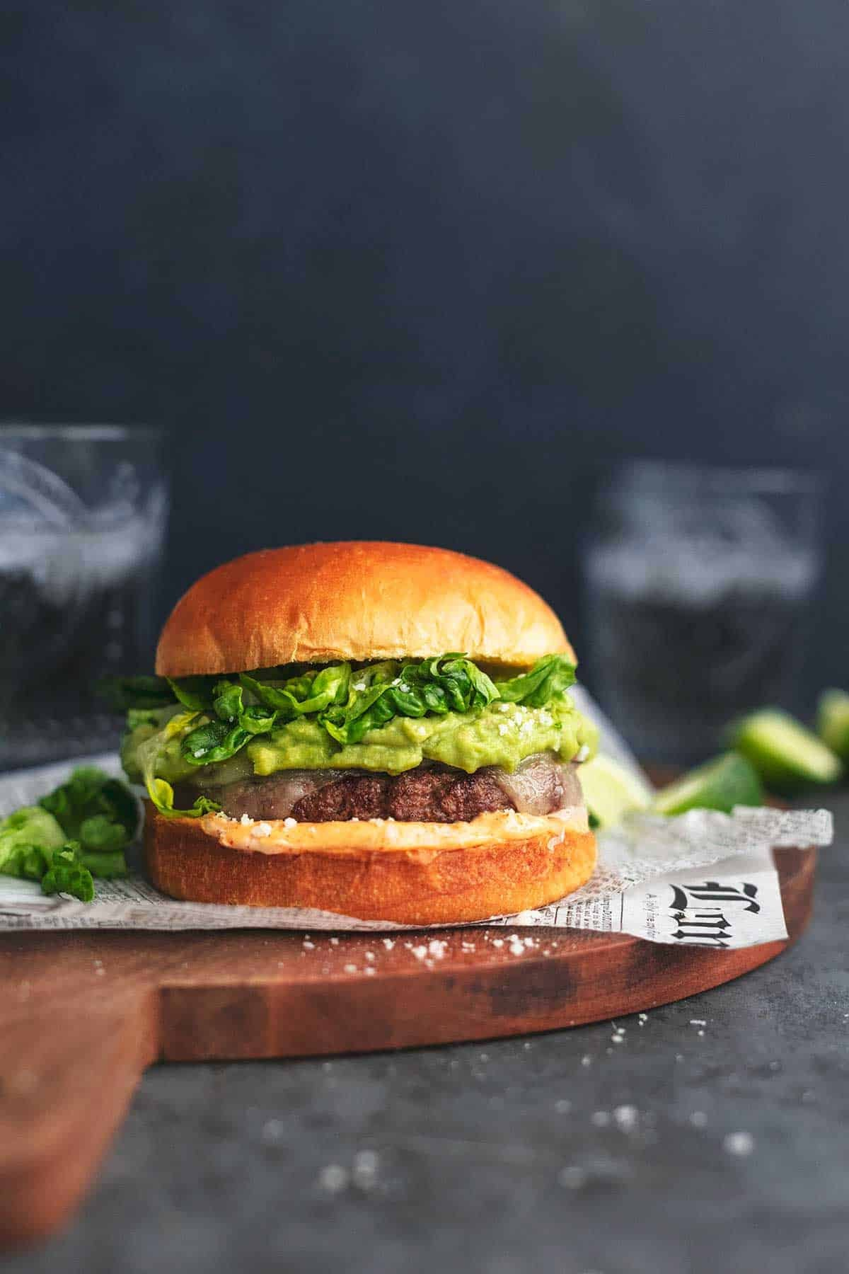 head-on view of turkey burger on cutting board with glass of soda
