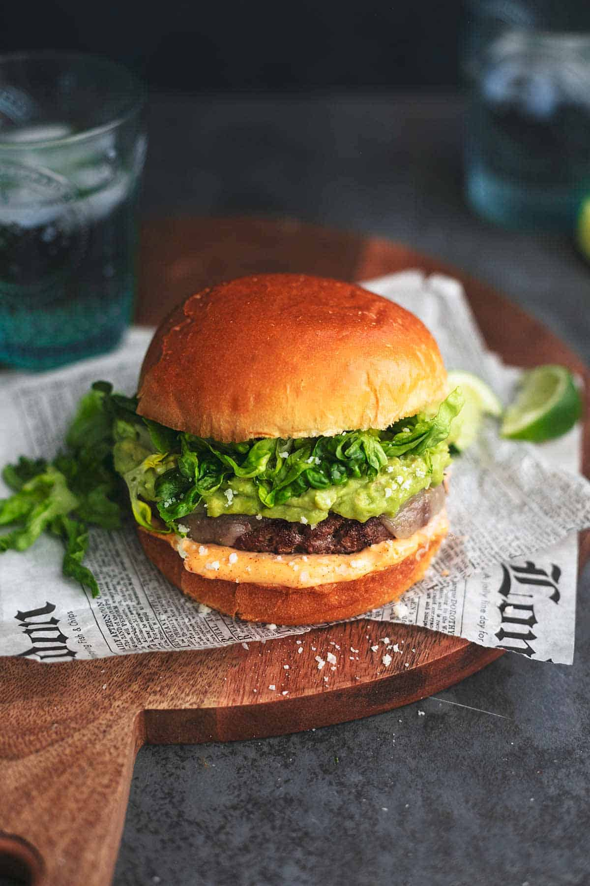 turkey burger with guacamole and lettuce on cutting board with newspaper