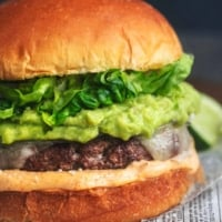 up close detail photo of turkey burger with cheese, mayo, guacamole, and lettuce