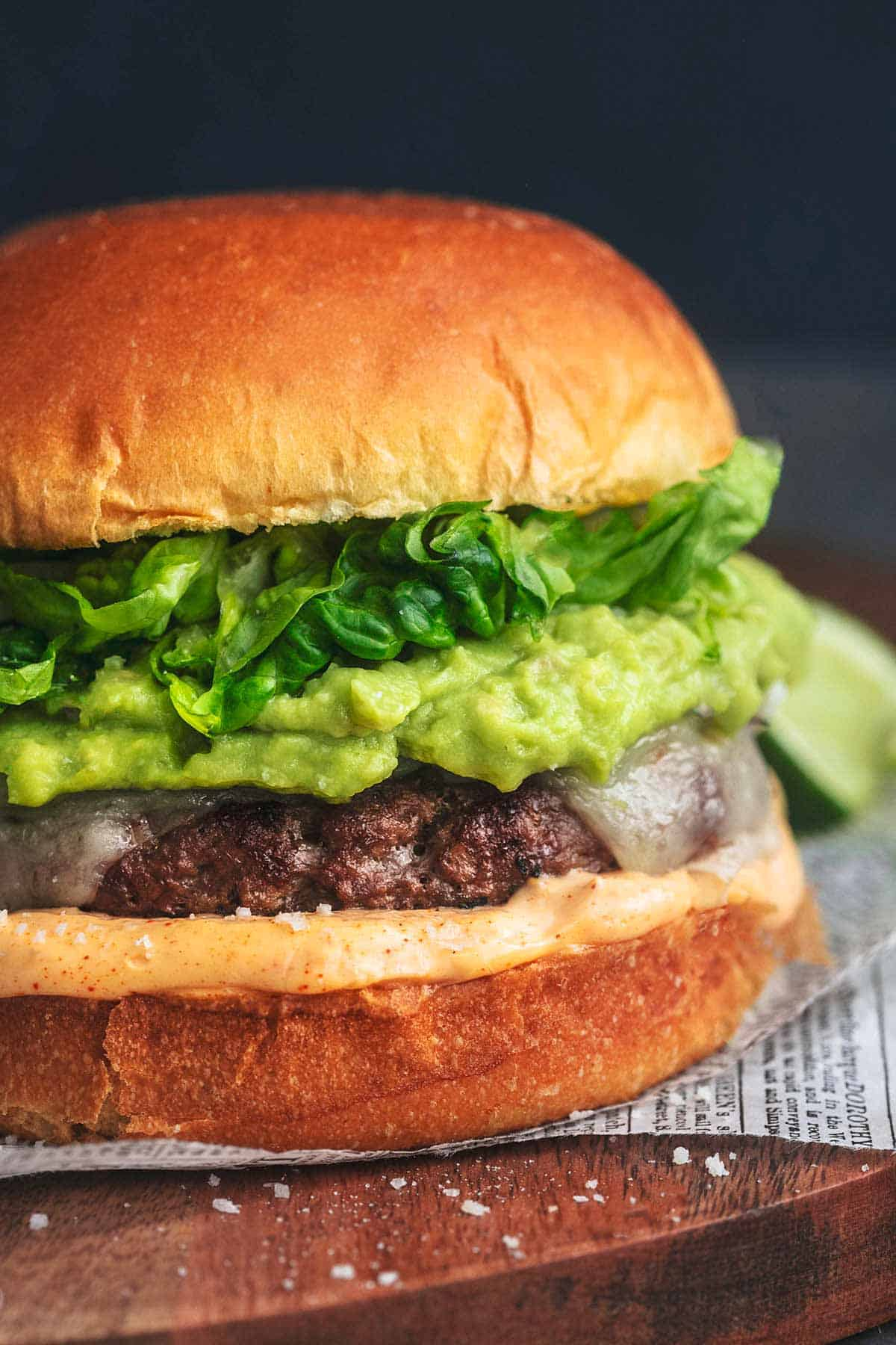 up close detail photo of burger with cheese, mayo, guacamole, and lettuce