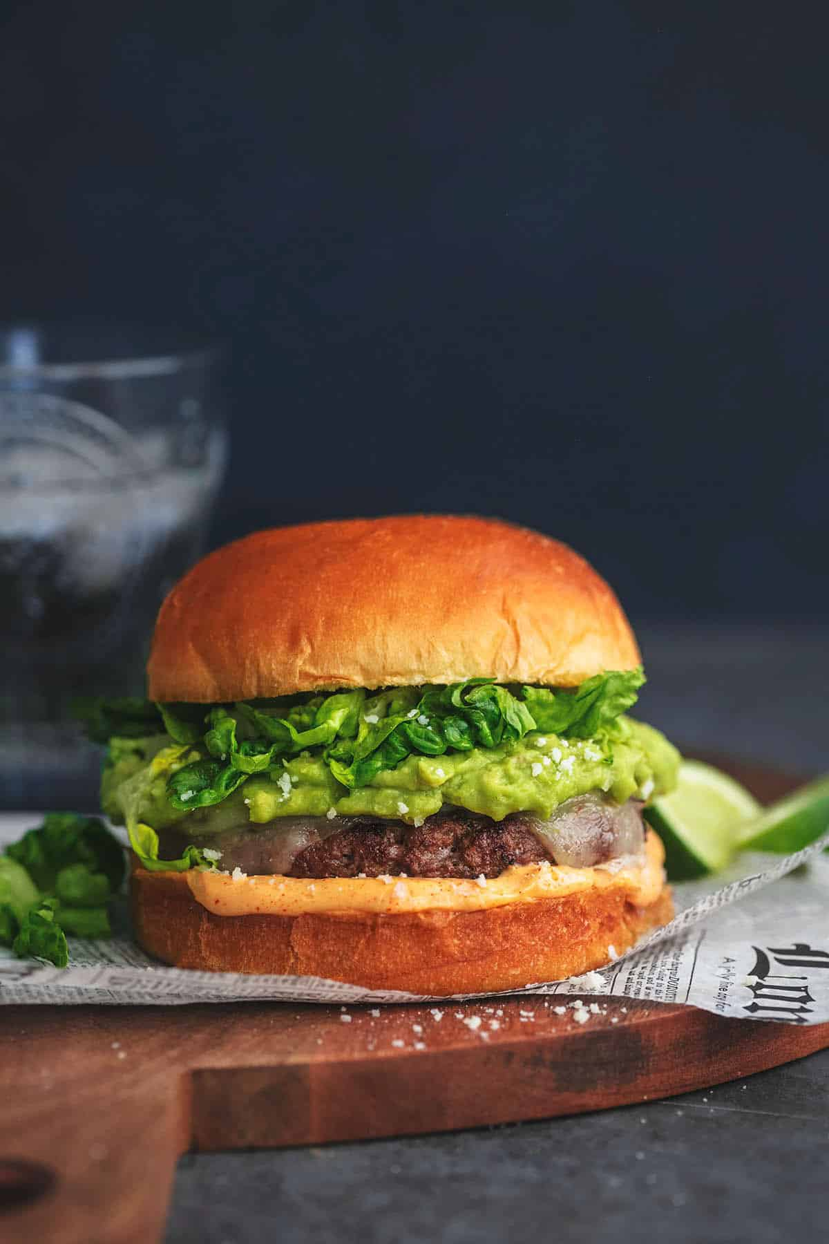 head-on view of burger with cheese and avocado and lettuce on cutting board
