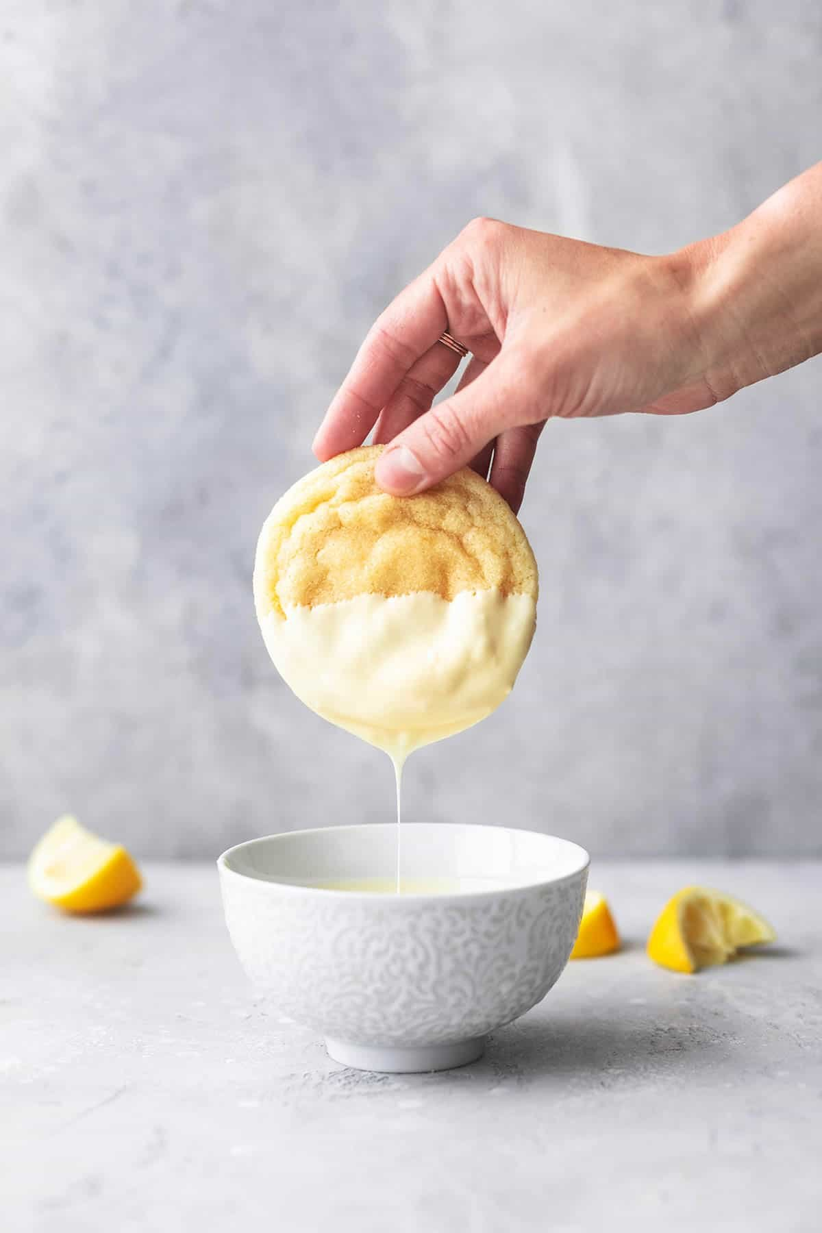 hand dipping lemon cookie into melted white chocolate in bowl