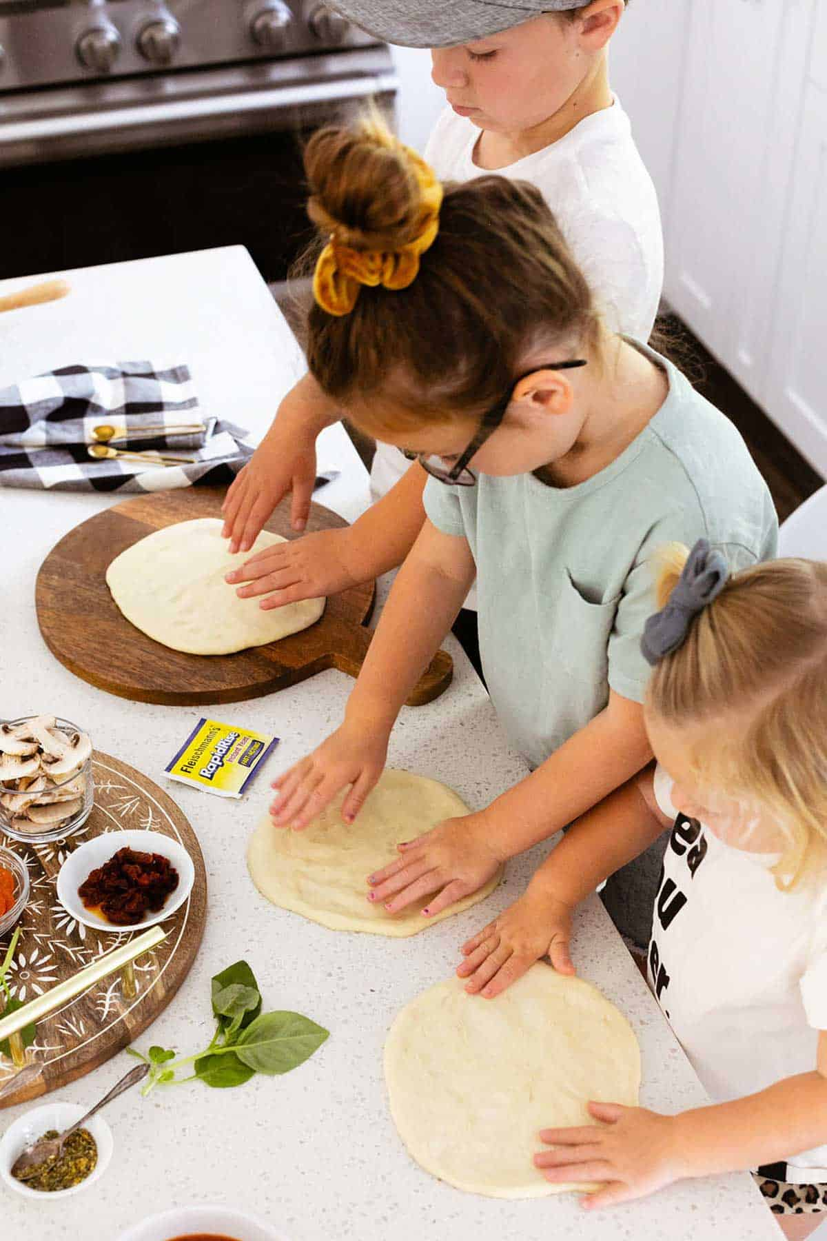 kids patting pizza dough on countertop