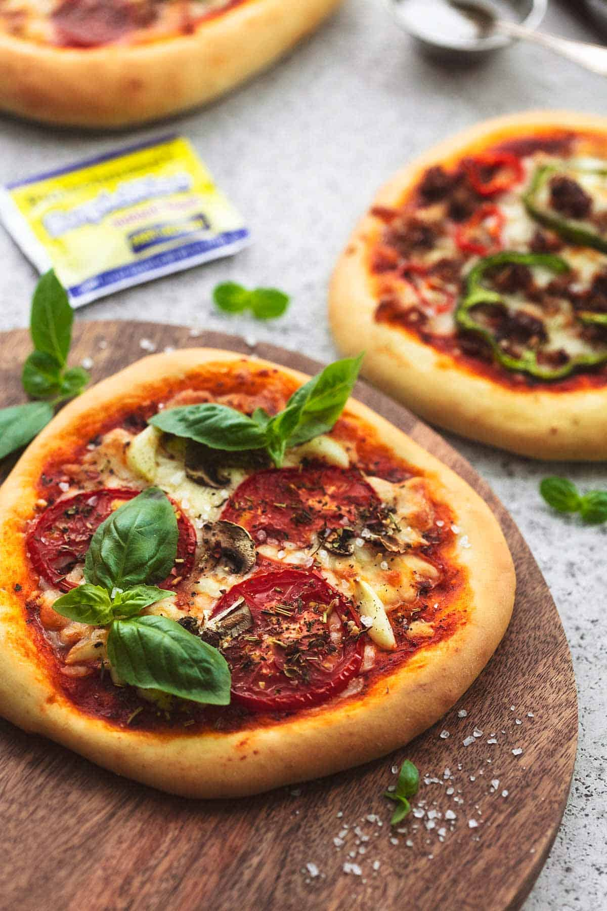 personal pizzas on wooden cutting board with yeast packet in background