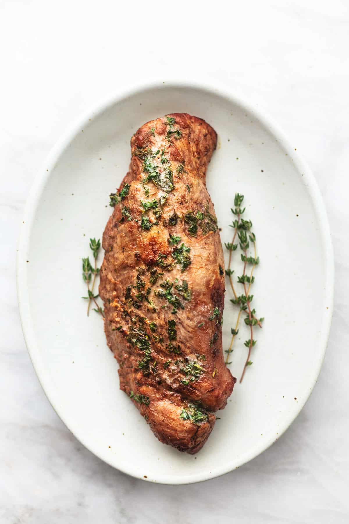 roasted pork tenderloin with fresh herbs on platter