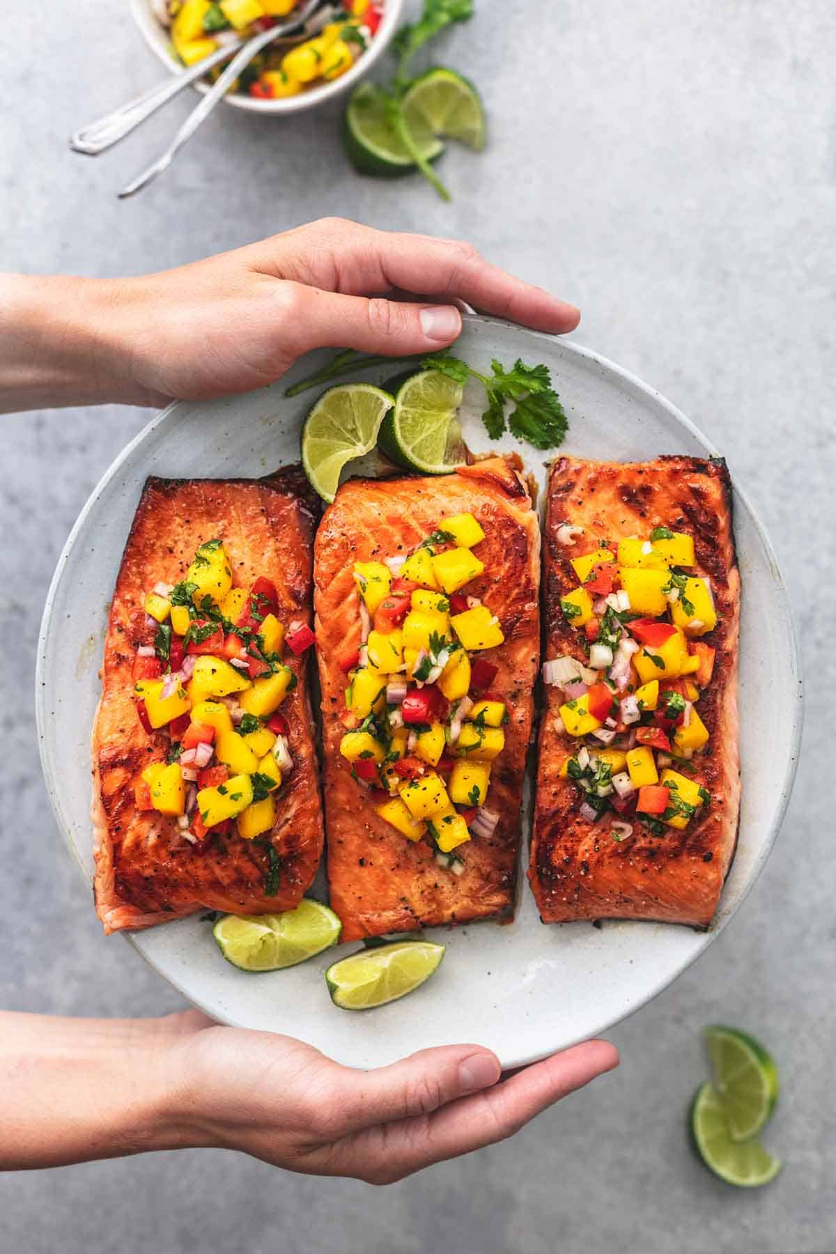top view of hands holding a plate of honey lime salmon with mango salsa on a plate.