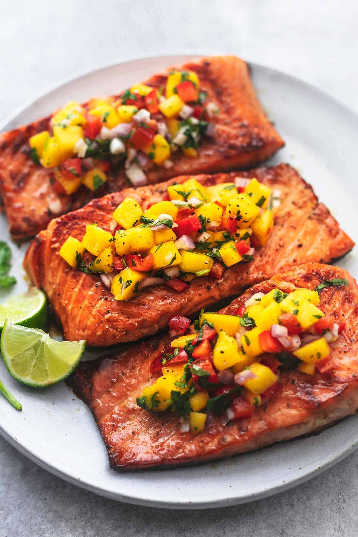 three pieces of salmon on a plate topped with mango salsa