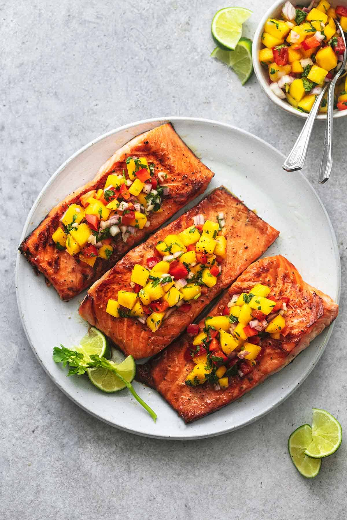 top view of honey lime salmon with mango salsa on a plate.