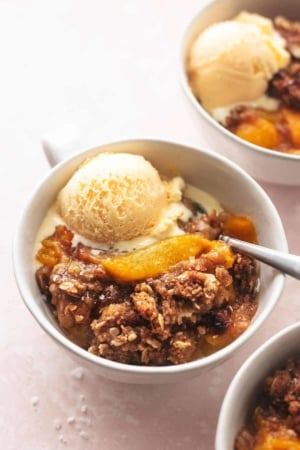 three bowls of peach crisp with spoons and vanilla ice cream