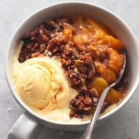 one bowl of peach crisp with scoop of ice cream and a spoon
