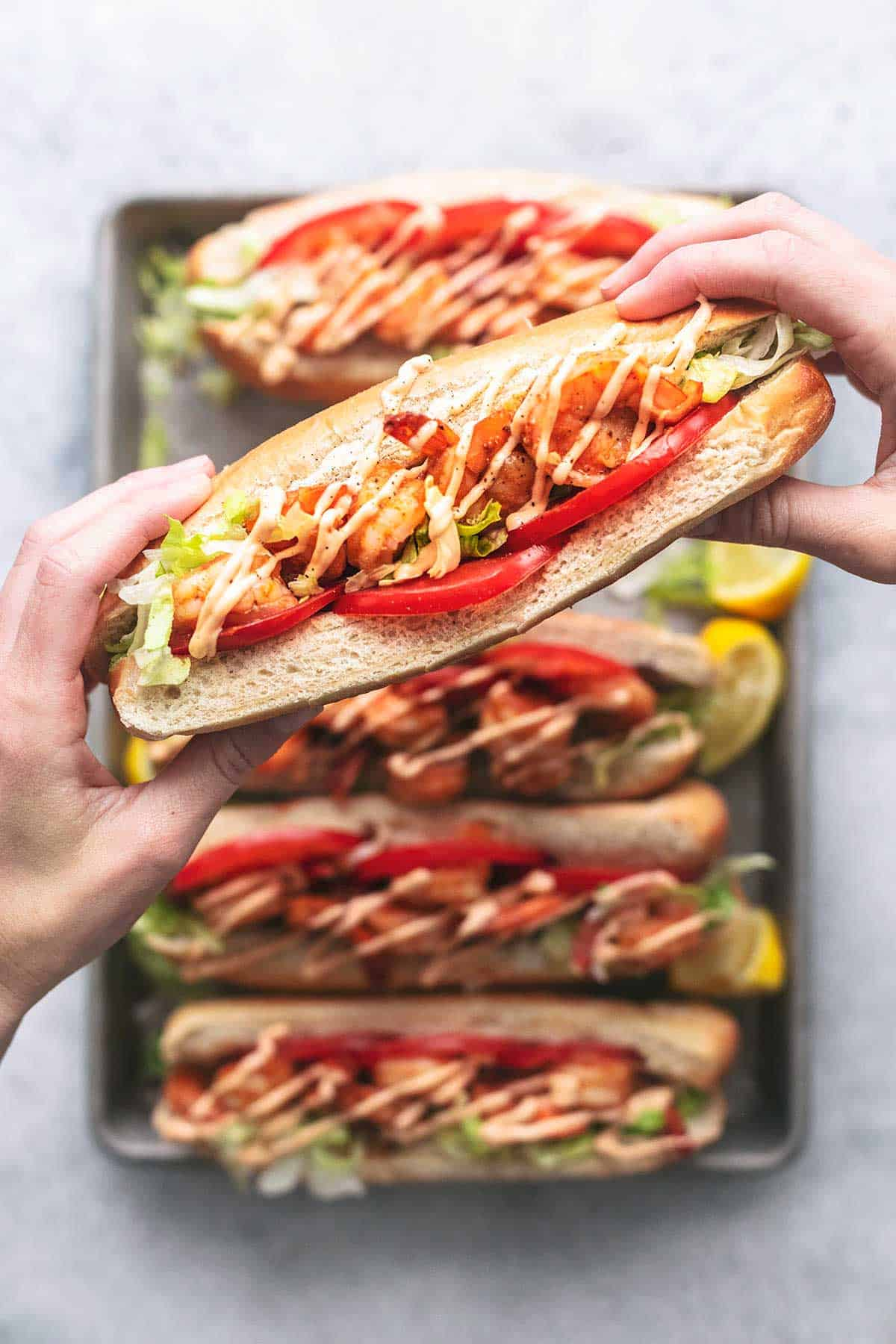 overhead hands holding one shrimp po boy over a pan of more