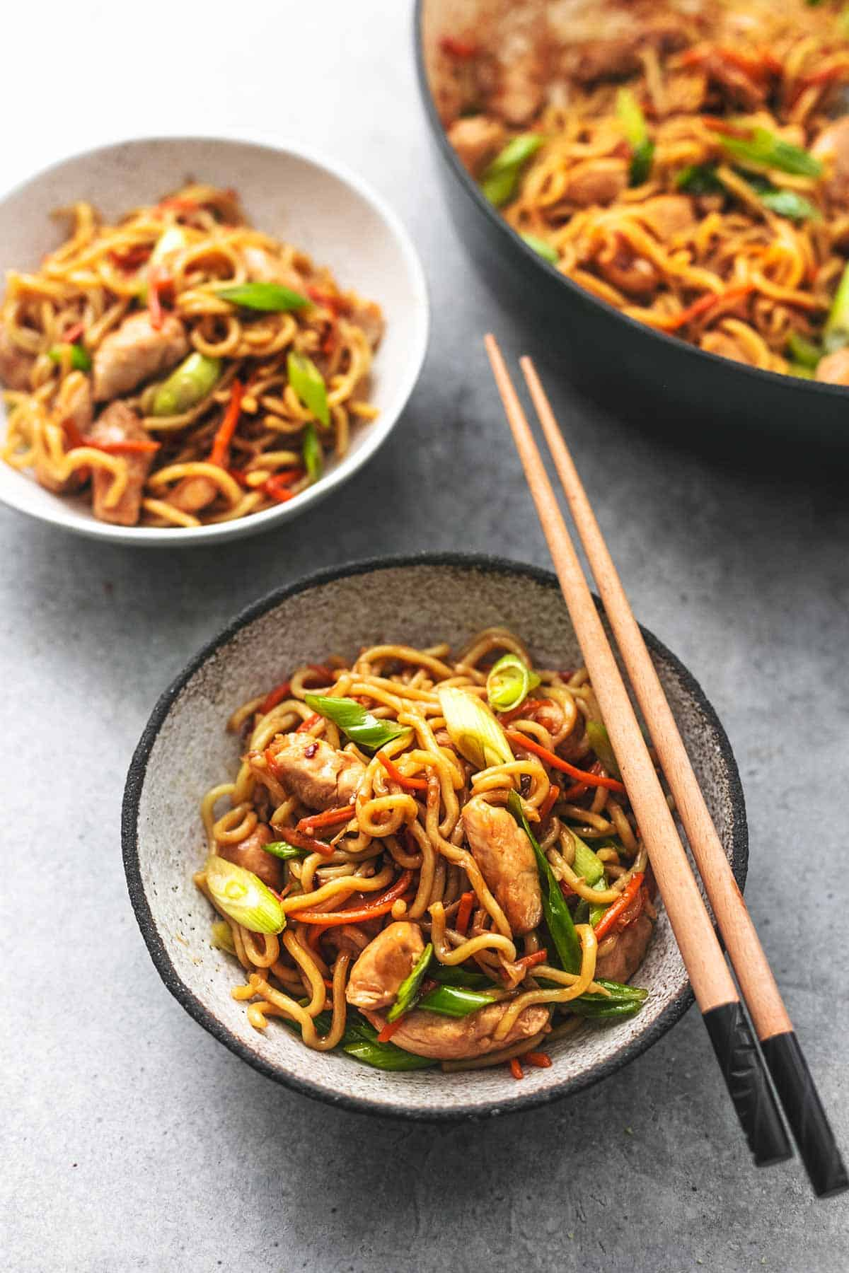a bowl with chopsticks on top, bowl filled with chicken chow mein noodles