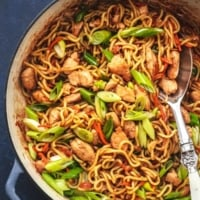 chicken chow mein in a skillet with a serving spoon