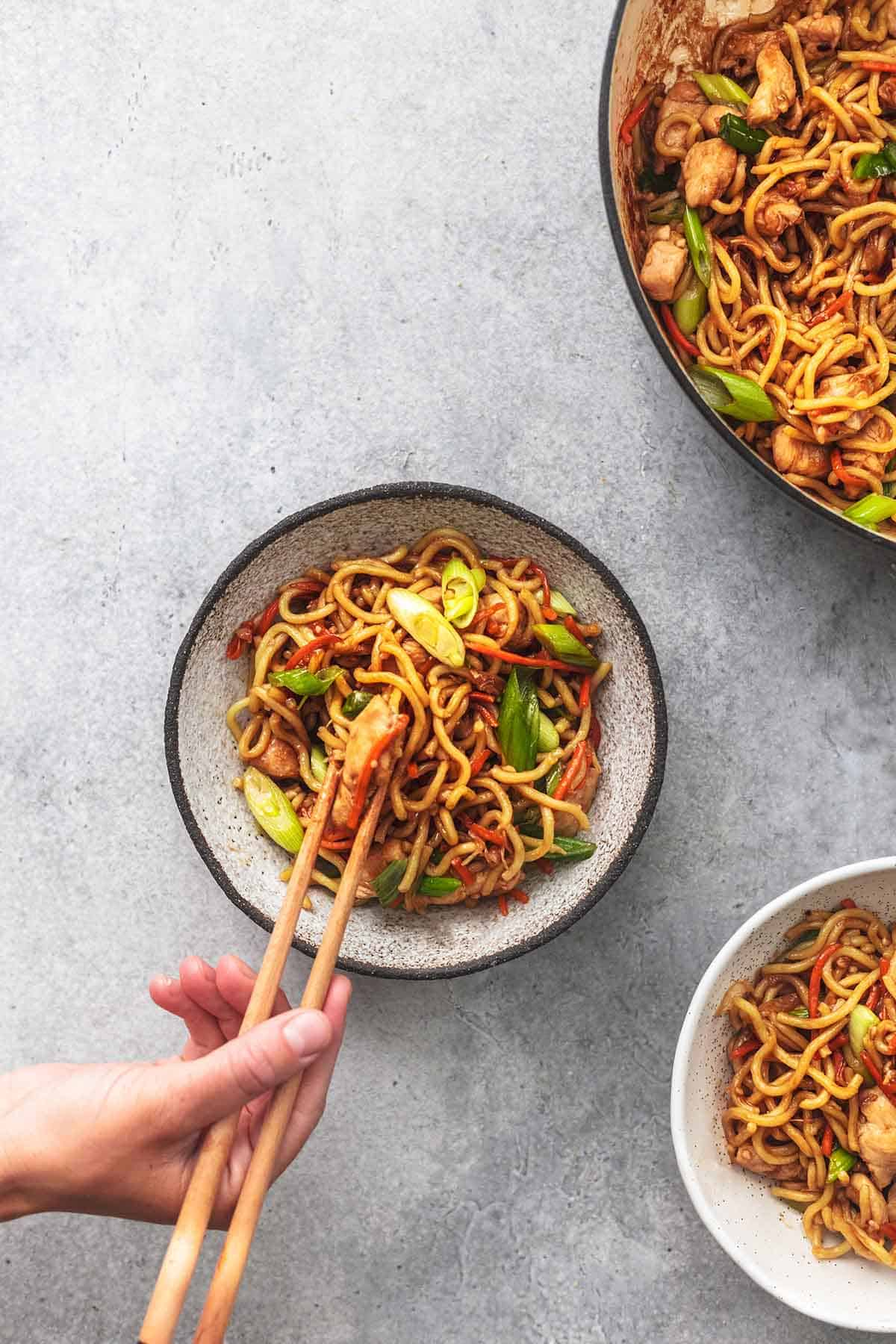 top view of hands grabbing a bite of chicken chow mein from a bowl with chopsticks.