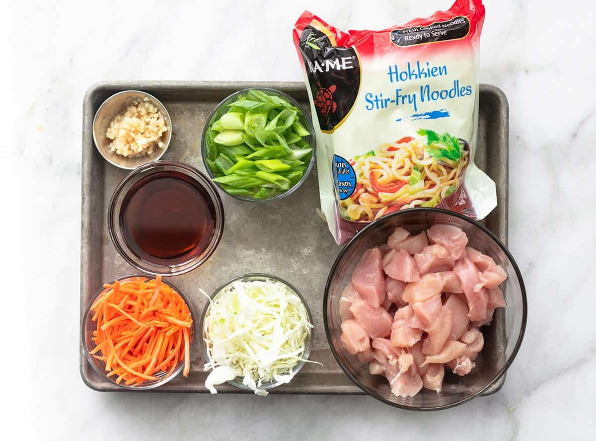 top view of ingredients for chicken chow mein on a baking sheet.