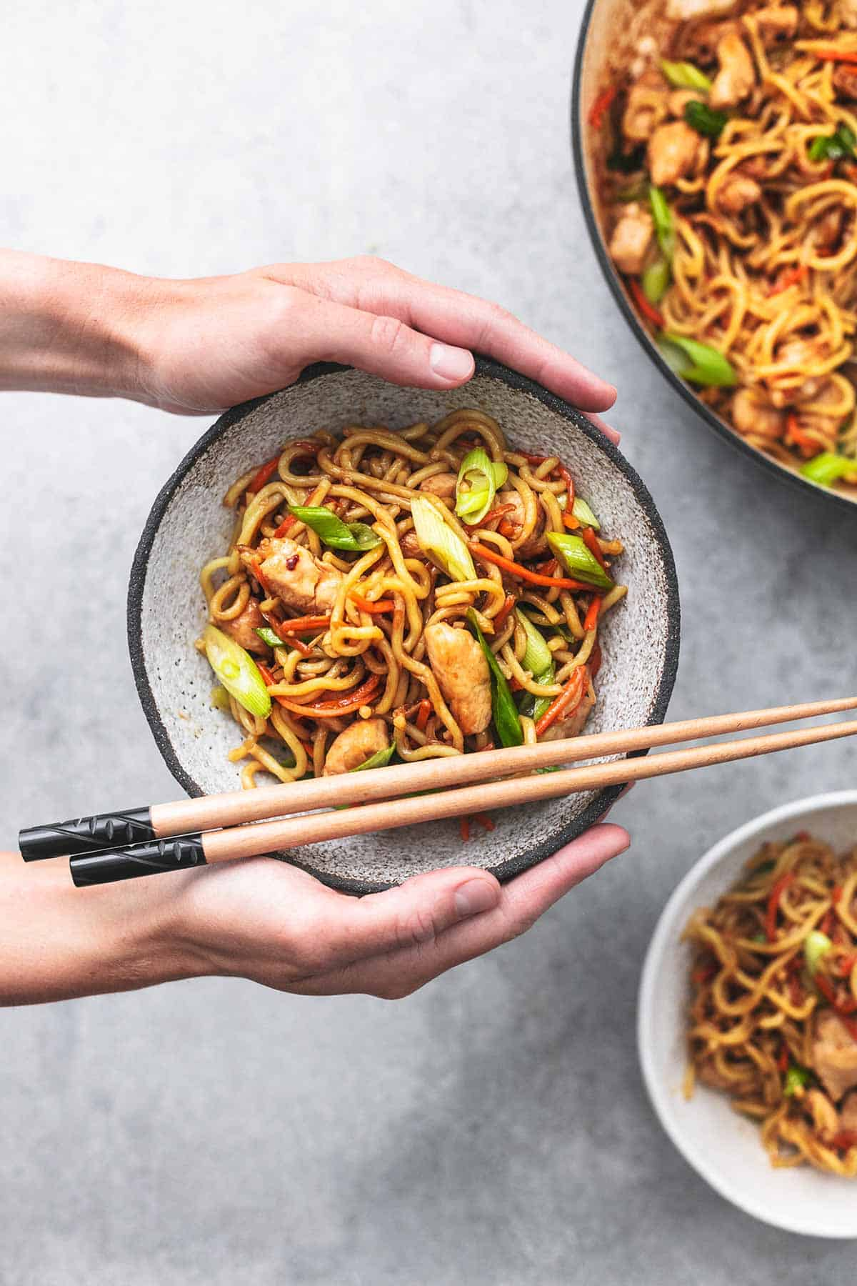 top view of hands holding a bowl of chicken chow mein above another bowl and skillet.