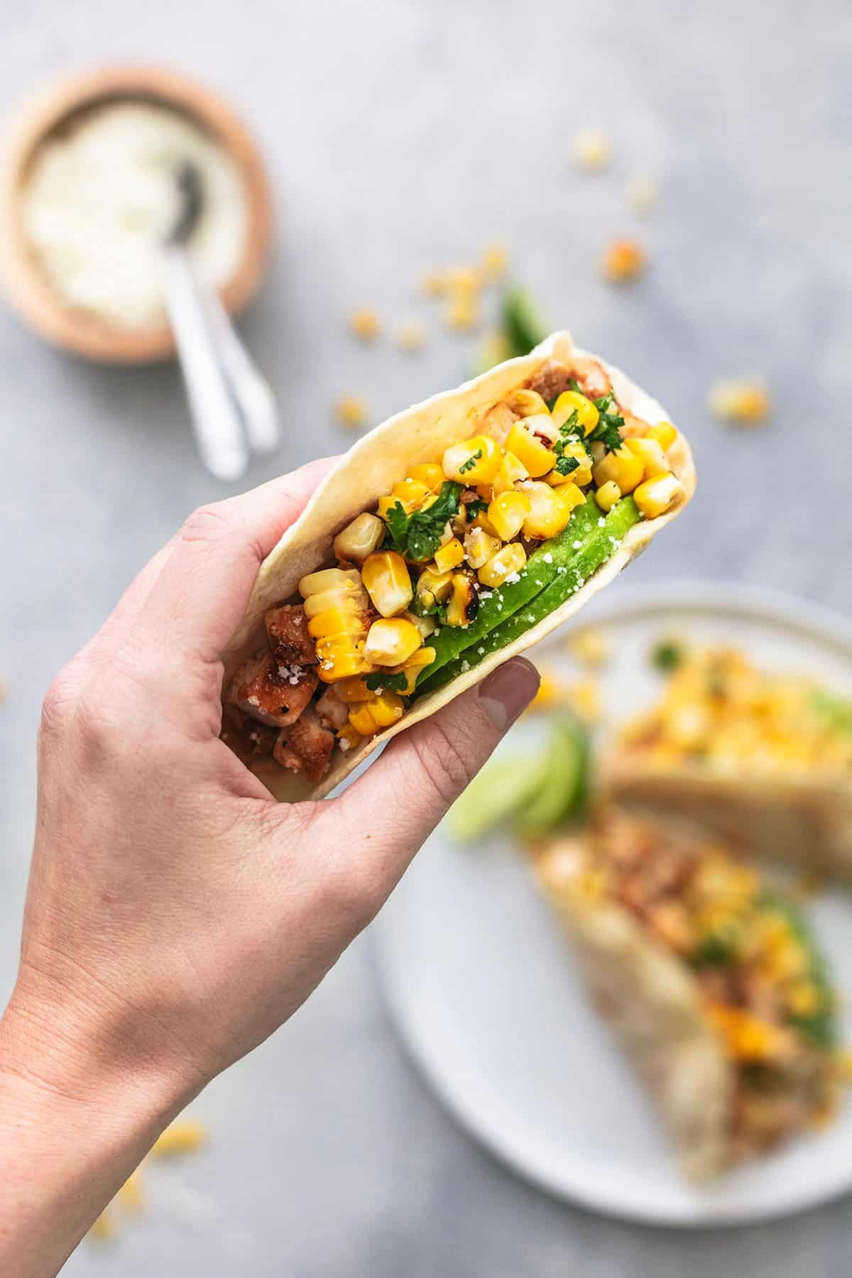 hand holding single tortilla with chicken and topped with corn and avocado