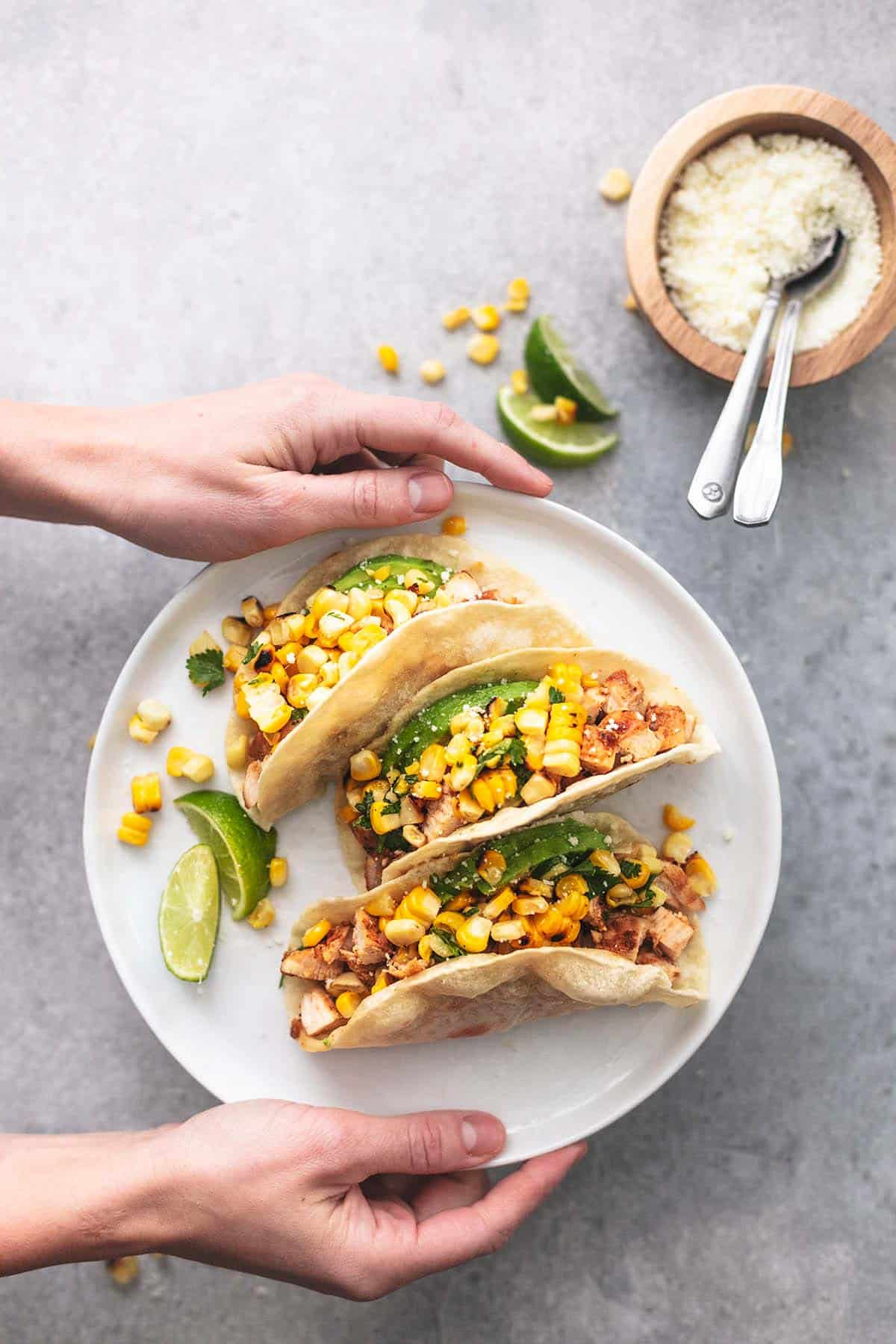top view of hands holding a white plate with chicken tacos on it.