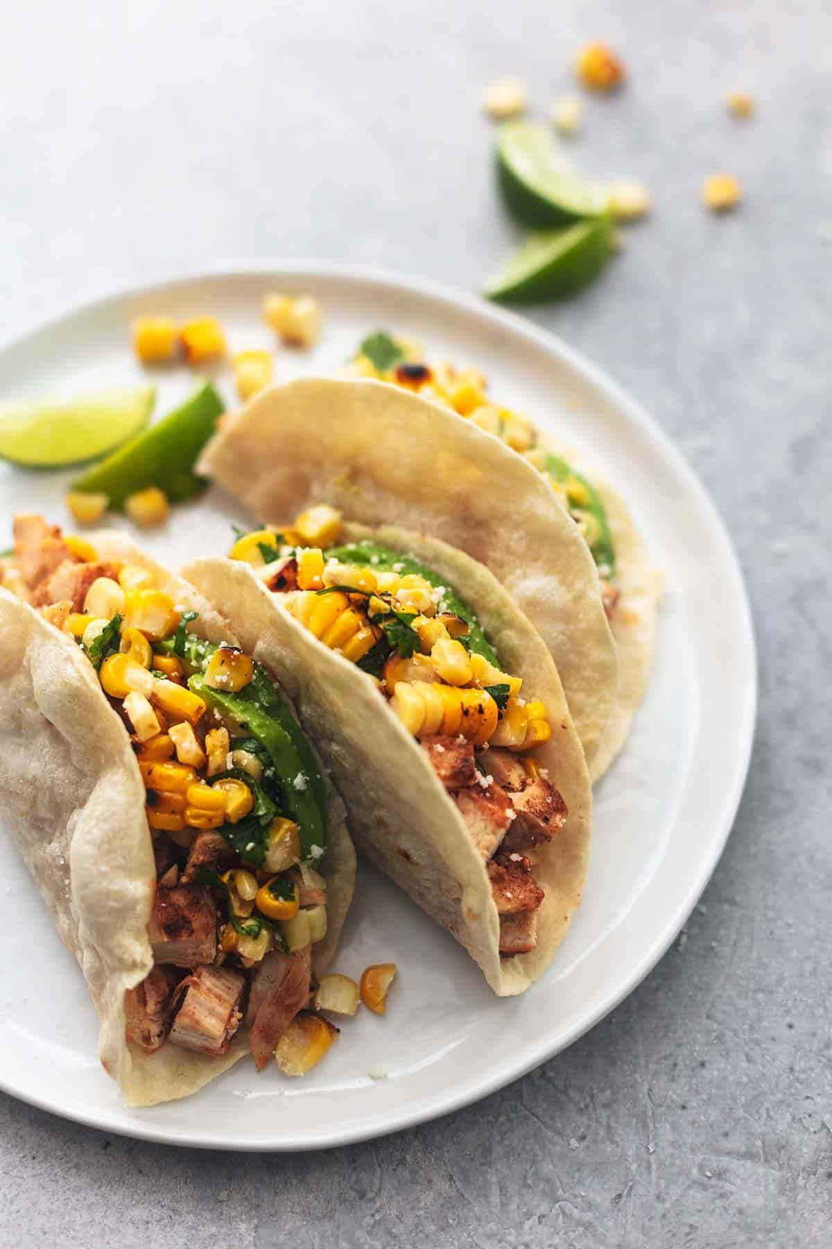 three tortillas filled with avocado, diced chicken, and corn salsa on white plate with limes