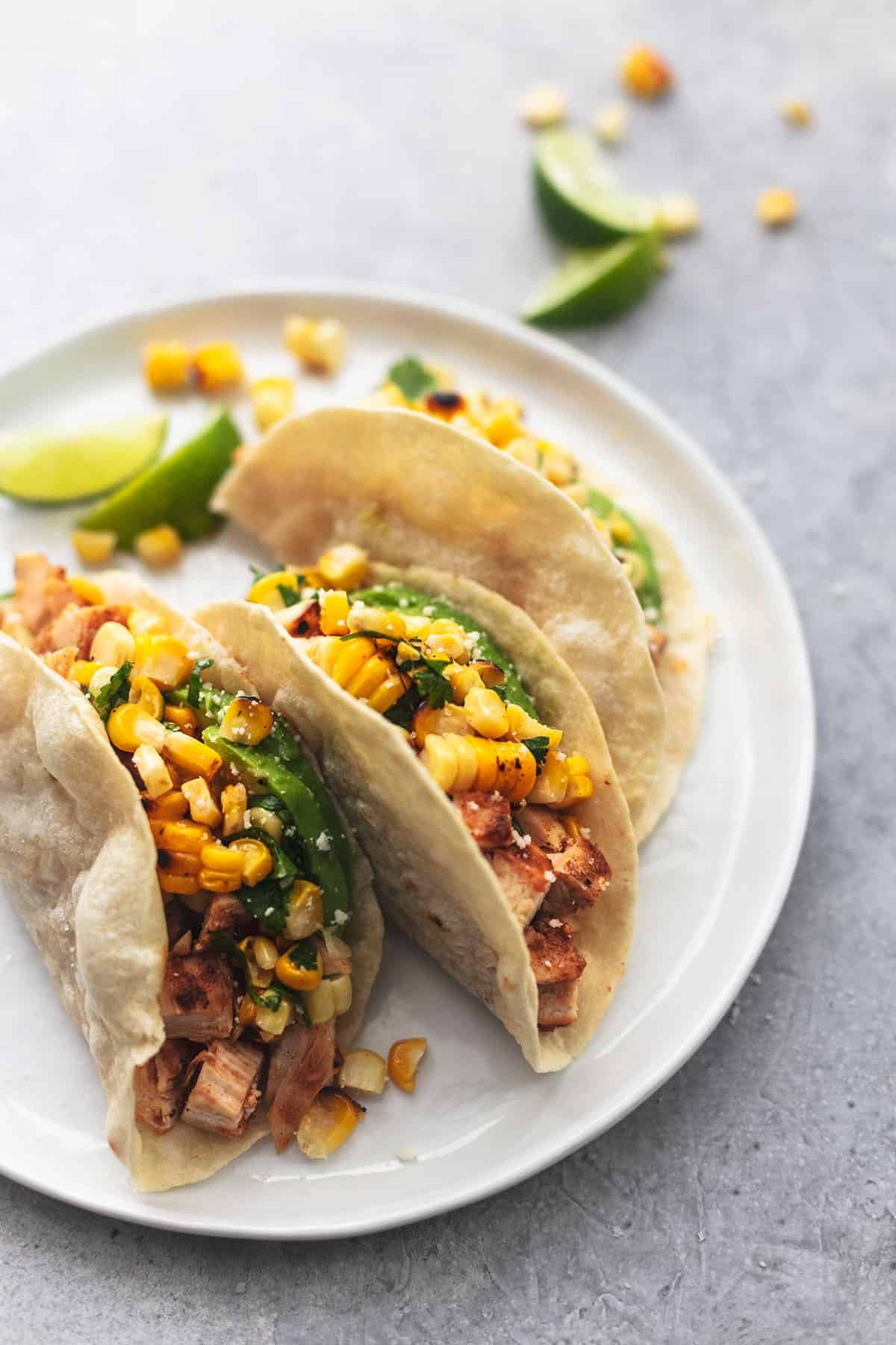 three tortillas on a plate with avocado and corn salsa