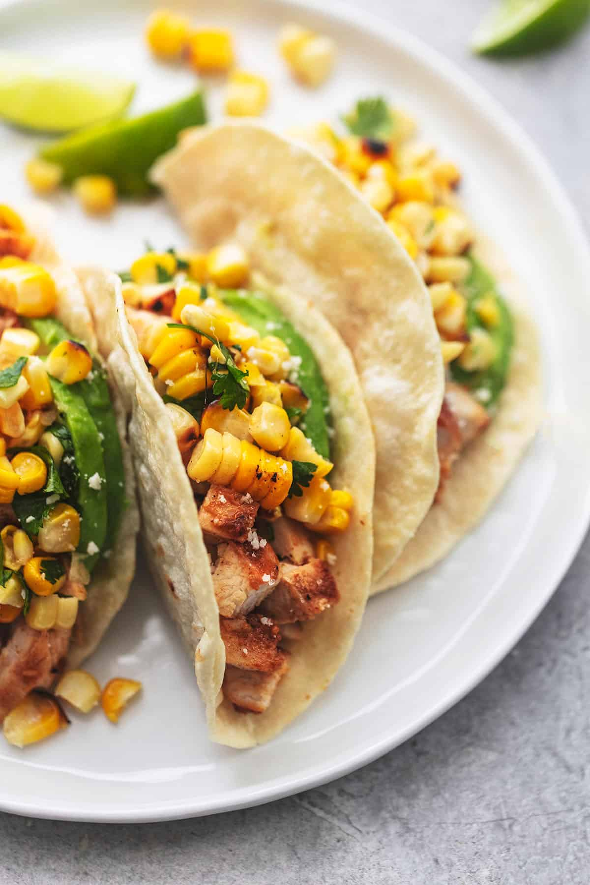 three tortillas filled with chicken, avocado and corn salsa on white plate