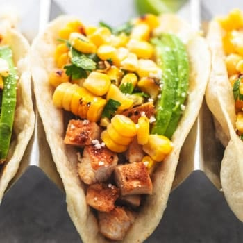 up close single chicken taco in taco holder topped with corn salsa